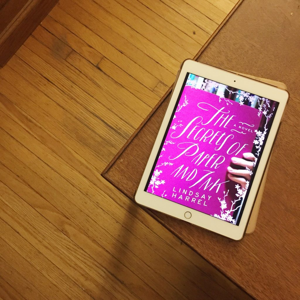 cover of the secrets of paper and ink on an ipad on a table