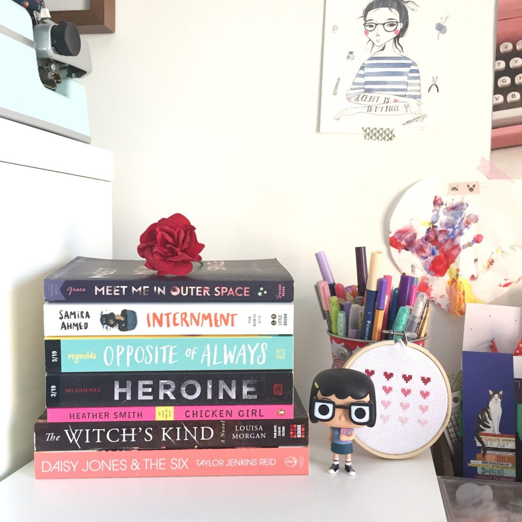 stack of books in an office with stationery and art in the background